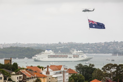 P&O's Pacific Pearl cruise ship in Sydney Harbour as helicopter towing flag flies above